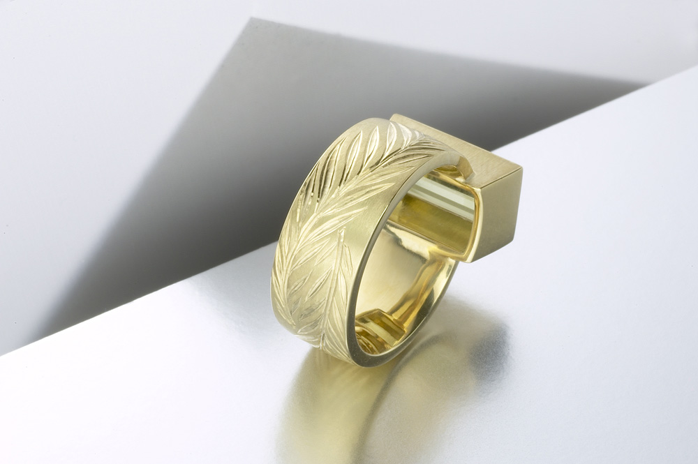 "<a href=""/jewellery/reverse-detail-olive-ring-18ct-yellow-gold-hand-engraved-cut-interlocking-olive-branches"">Reverse detail: 'Olive' ring, 18ct yellow gold, hand engraved cut with interlocking olive branches, olive green tourmaline baguette. Photo: Paul Hartley</a>"