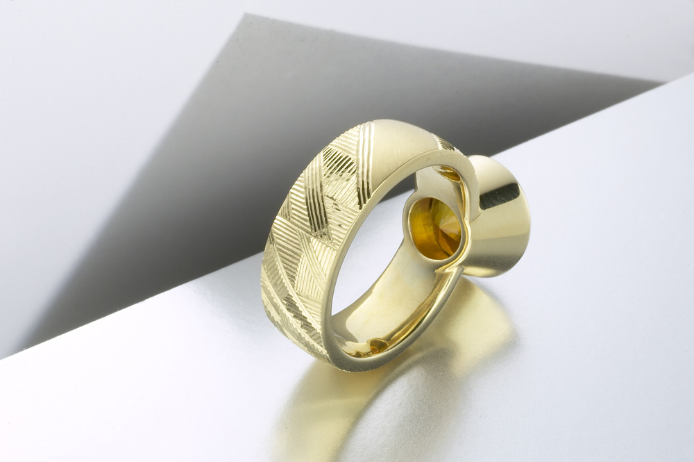 "<a href=""/jewellery/reverse-detail-earth-dress-ring-hand-engraved-18ct-yellow-gold-brown-green-tourmaline"">Reverse detail: 'Earth' Dress ring, hand engraved, 18ct yellow gold, brown green tourmaline. Photo: Paul Hartley</a>"