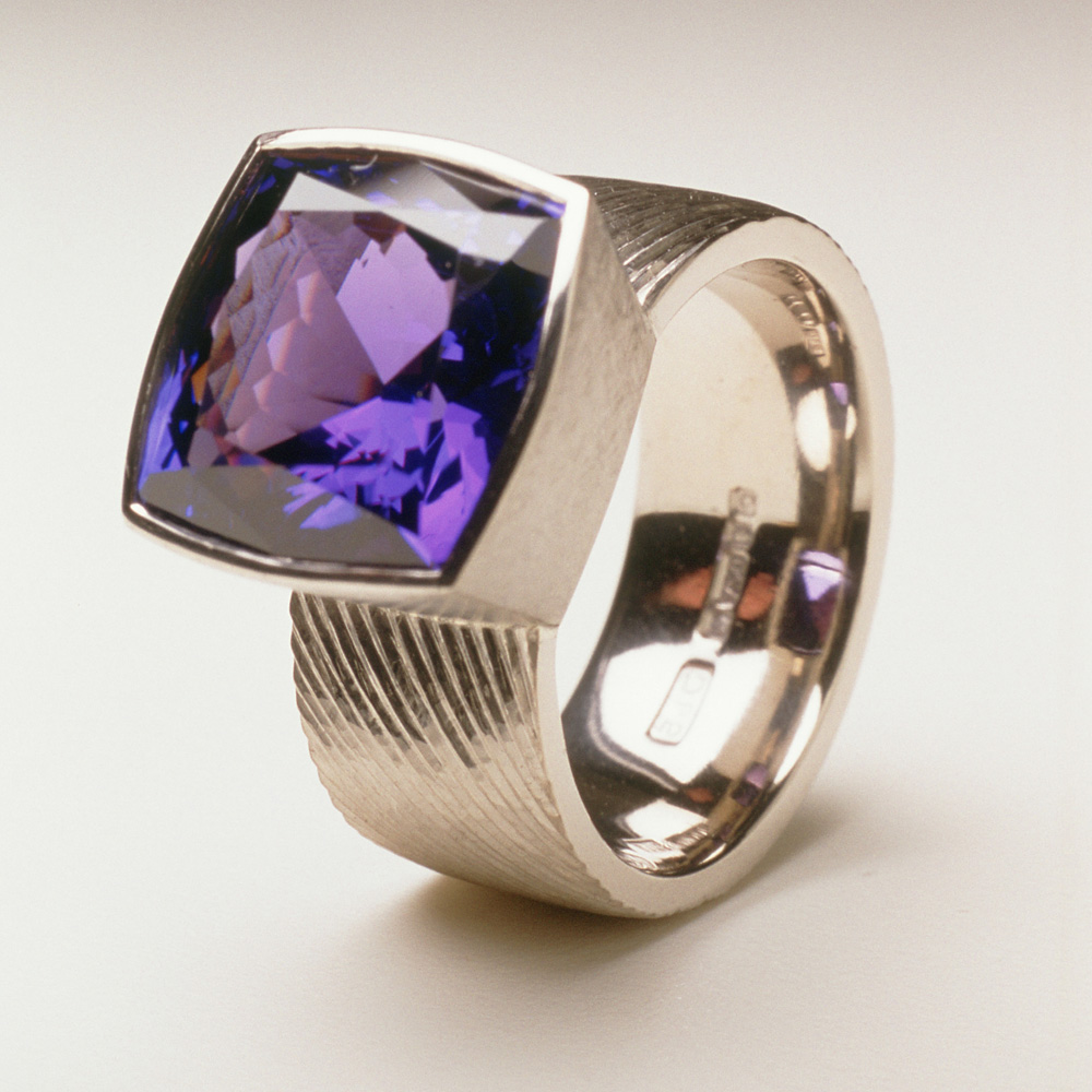 "<a href=""/jewellery/ring-19"">Dress ring, 18ct white gold, hand engraved, cushion cut tanzanite, 7.18 cts.</a>"