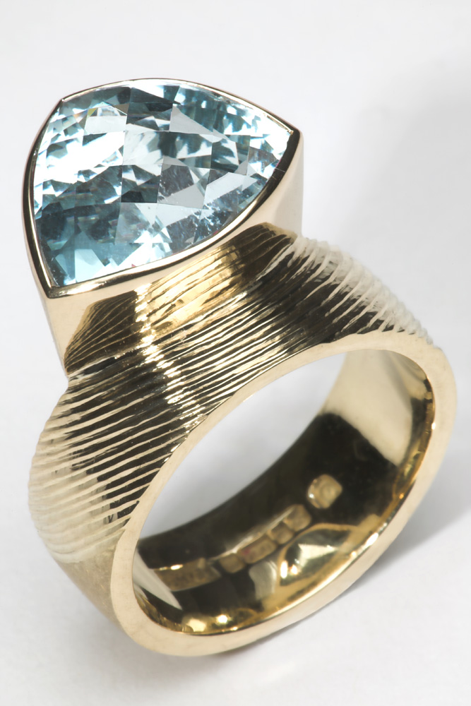 "<a href=""/jewellery/dress-ring-18ct-yellow-gold-ring-shank-part-engraved-and-part-scrubbed-set-trillion"">Dress Ring. 18ct yellow gold, ring shank part engraved and part scrubbed. Set with Trillion chequerboard cut Aquamarine 5.40 cts.</a>"