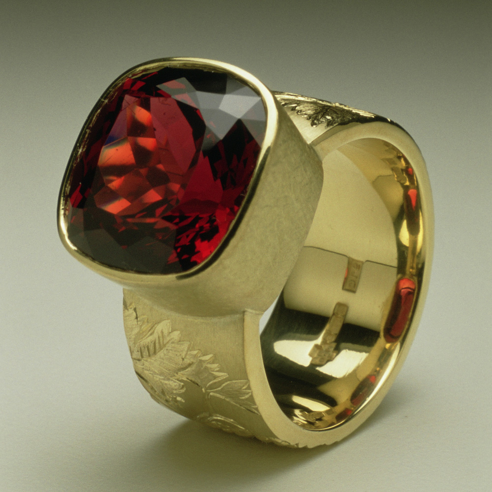 "<a href=""/jewellery/chianti-dress-ring-commission-cushion-cut-garnet-18ct-yellow-gold-hand-engravers-and"">""Chianti"" Dress Ring, Commission, cushion cut Garnet, 18ct yellow gold hand engravers and carved with vine leaves and grapes</a>"