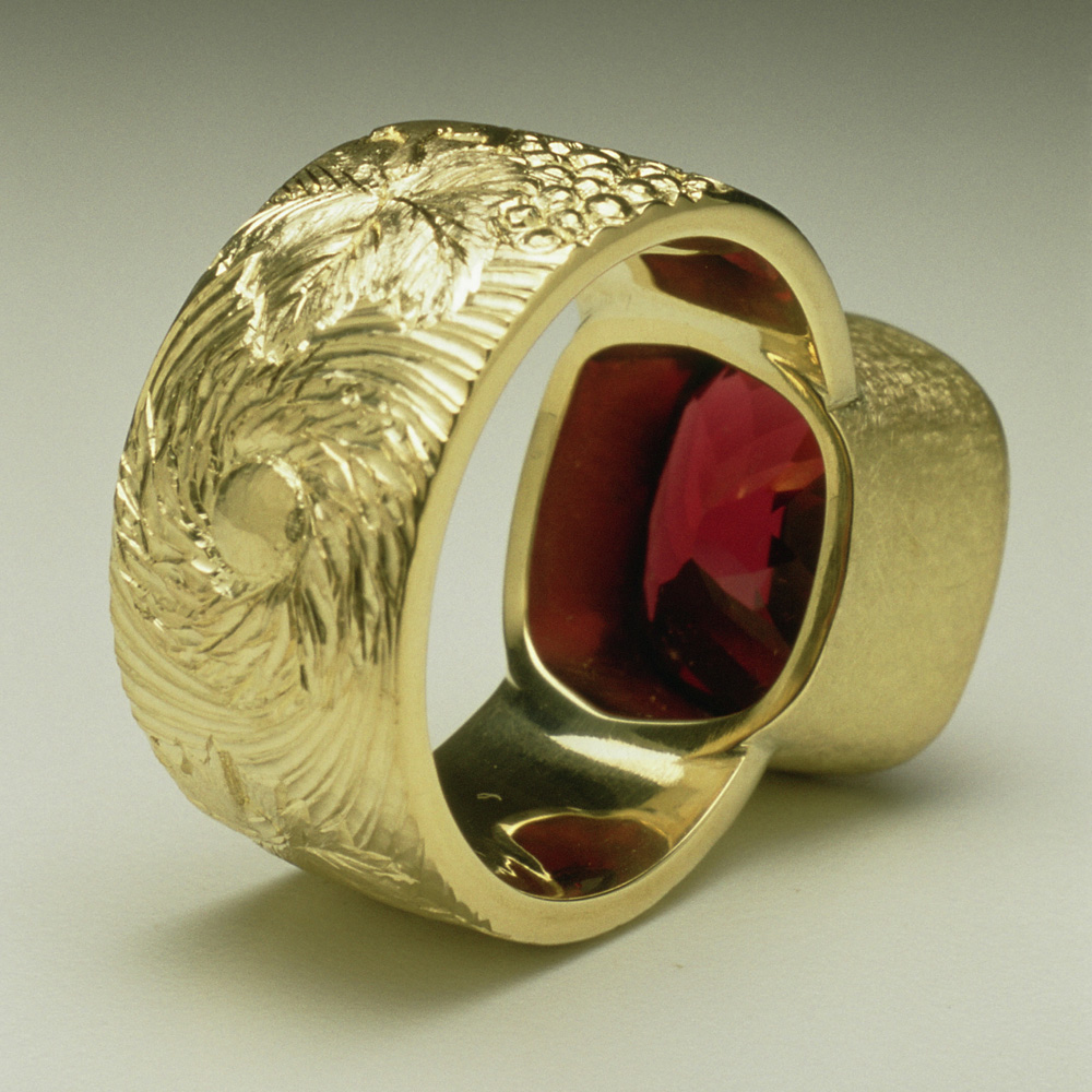 "<a href=""/jewellery/reverse-detail-chianti-dress-ring-commission-cushion-cut-garnet-18ct-yellow-gold-hand"">Reverse Detail: &quot;Chianti&quot; Dress Ring, Commission, cushion cut Garnet, 18ct yellow gold hand engravers and carved with vine leaves and grapes</a>"