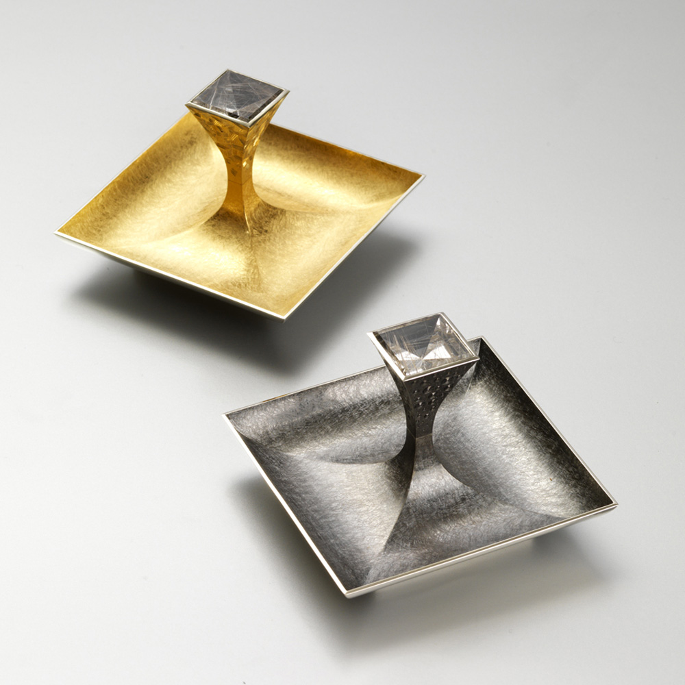 "<a href=""/jewellery/pair-salts-13-made-silver-pinch-salt-goldsmiths-hall-spring-2009-dishes-88-mm-square"">Pair of Salts 1/3. Made for &quot;SILVER WITH A PINCH OF SALT&quot; at Goldsmiths Hall Spring 2009. Dishes 88 mm square.. Silver yellow gilding, black rhodium plate, set with pair of square mirror cut rutilated quartz. Setting hand engraved. Photo : courtesy The Go</a>"