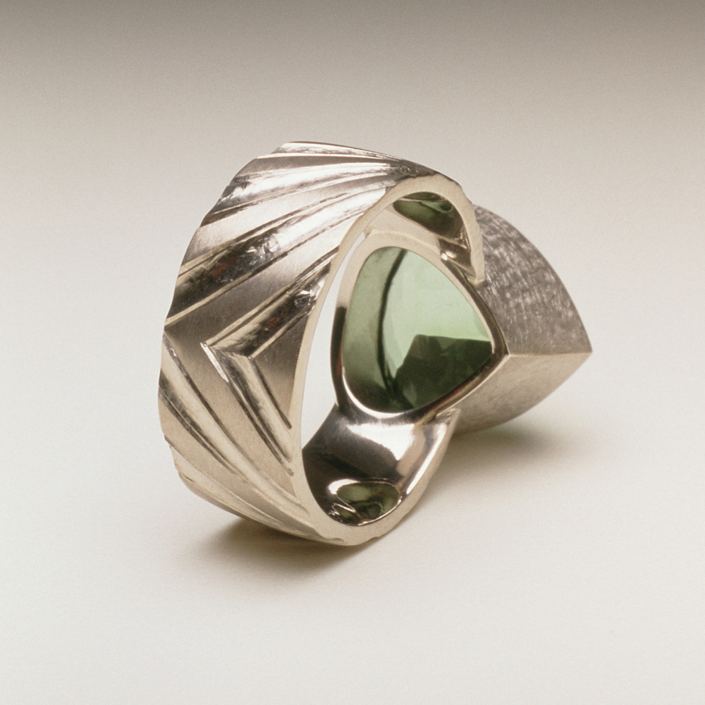 "<a href=""/jewellery/reverse-detail-9"">Reverse detail: Dress ring, 18ct white gold, hand carved and engraved, pale green tourmaline.</a>"