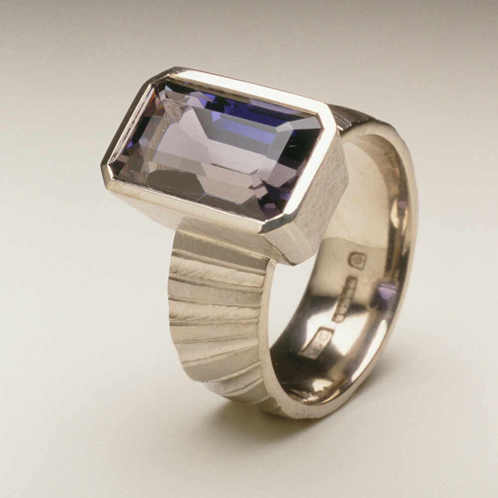 "<a href=""/jewellery/ring-17"">Ring shank inspired by pillars of the nave of Durham Cathedral. 18ct white gold, hand carved and engraved, setting a baguette Iolite.</a>"