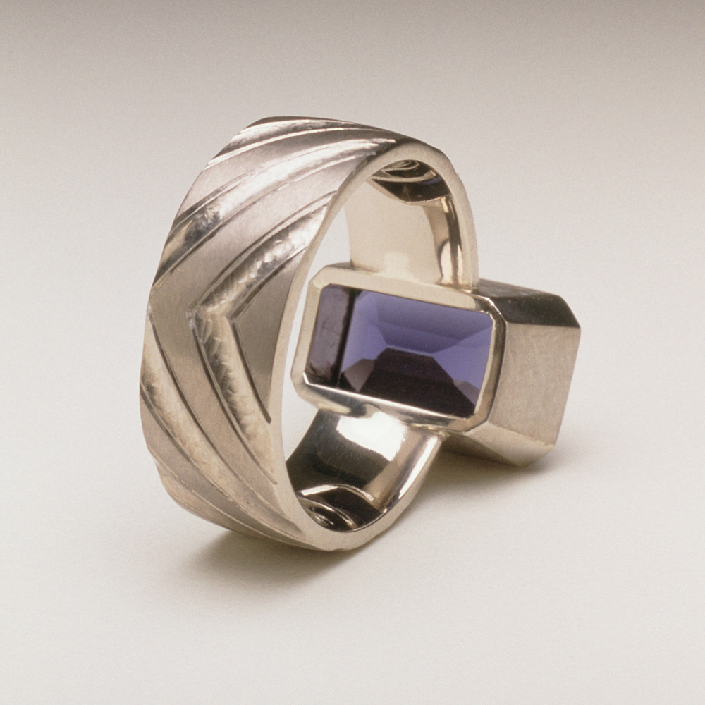 "<a href=""/jewellery/reverse-detail-8"">Reverse Detail: Ring shank inspired by pillars of the nave of Durham Cathedral. 18ct white gold, hand carved and engraved, setting a baguette Iolite.</a>"