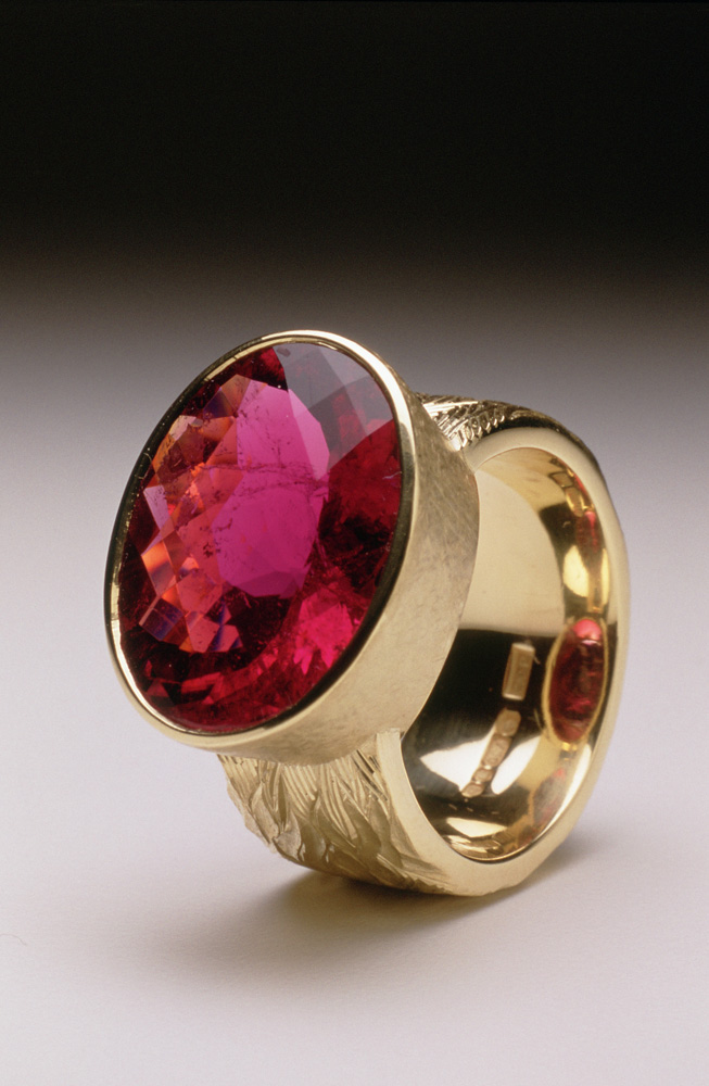 "<a href=""/jewellery/ring-16"">""Fire"" Dress ring, 18ct yellow gold, hand carved and engraved, red oval chequerboard rubelite tourmaline.</a>"