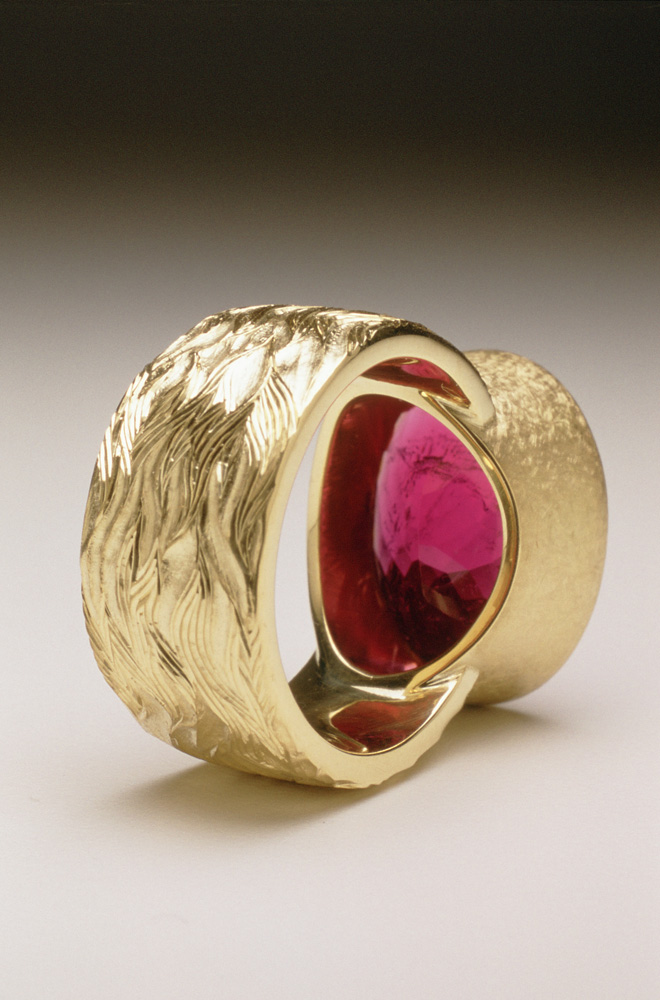 "<a href=""/jewellery/reverse-detail-7"">Reverse detail: ""Fire"" Dress ring, 18ct yellow gold, hand carved and engraved, red oval chequerboard rubelite tourmaline.</a>"