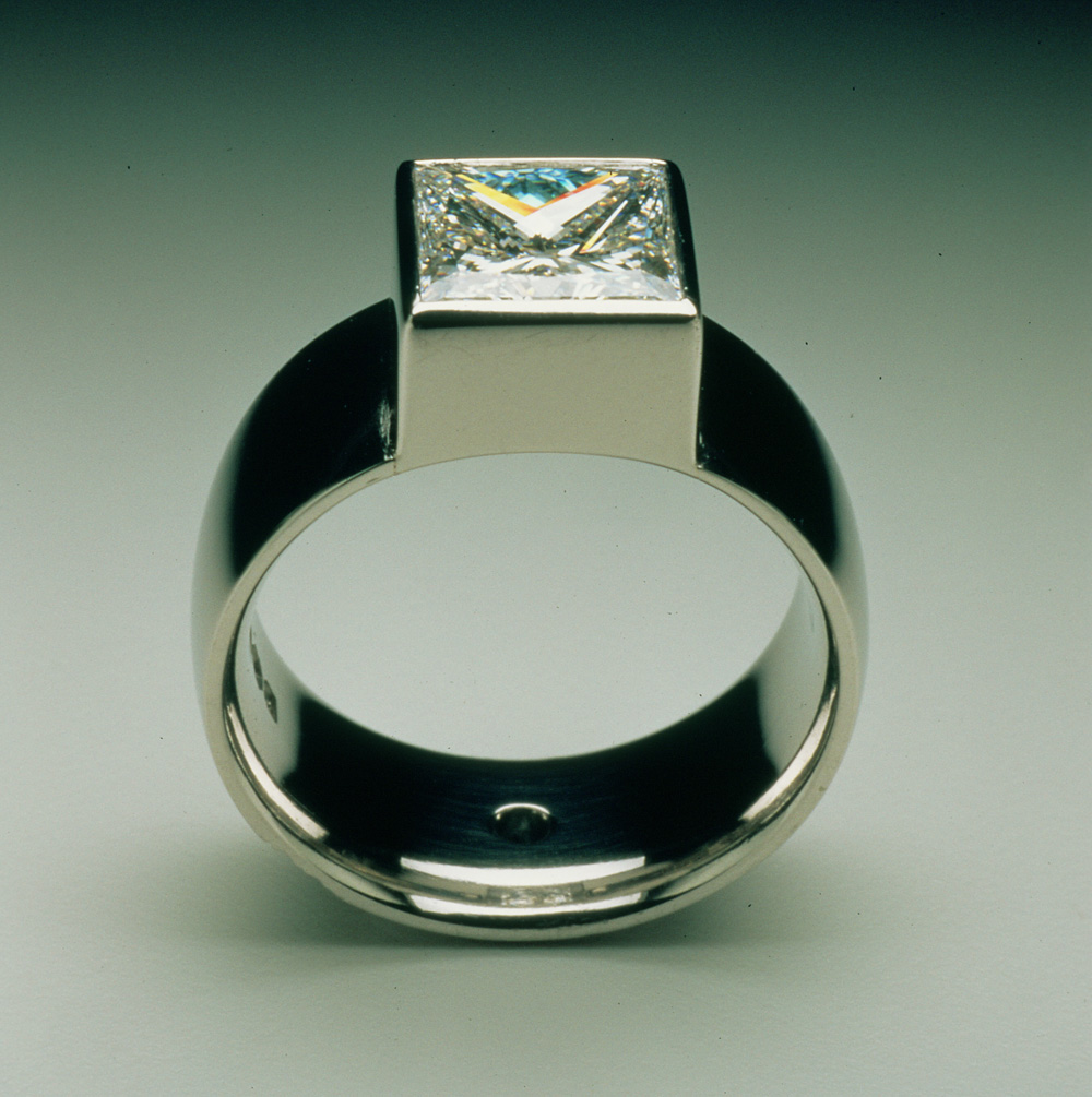 "<a href=""/jewellery/ring-14"">Engagement ring. Commission, square Diamond set in platinum. Small blue diamond in centre of back of the shank.</a>"