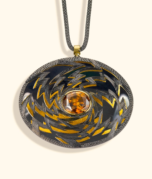 "<a href=""/node/260"">""Golden Lightening"" Oval 6cm x 4 cm. Silver hand engraved, hand pierced, mirror behind to reflect the underside.  Stone oval Zircon in orange / brown. set in 18ct gold.  View 1 Face on black reflections, White background</a>"