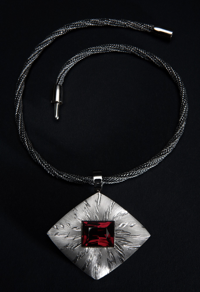 "<a href=""/jewellery/alchemy-pendant-photo-12-18-ct-white-gold-rectangular-garnet-1877-cts-face-piece-hand"">&quot;ALCHEMY&quot; PENDANT photo 1/2. 18 ct White Gold, rectangular Garnet 18.77 cts. Face of piece Hand Engraved, carved and striated, wd 6.0 cm x ht 6.0 cm overall. Photo: Simon Armitt</a>"