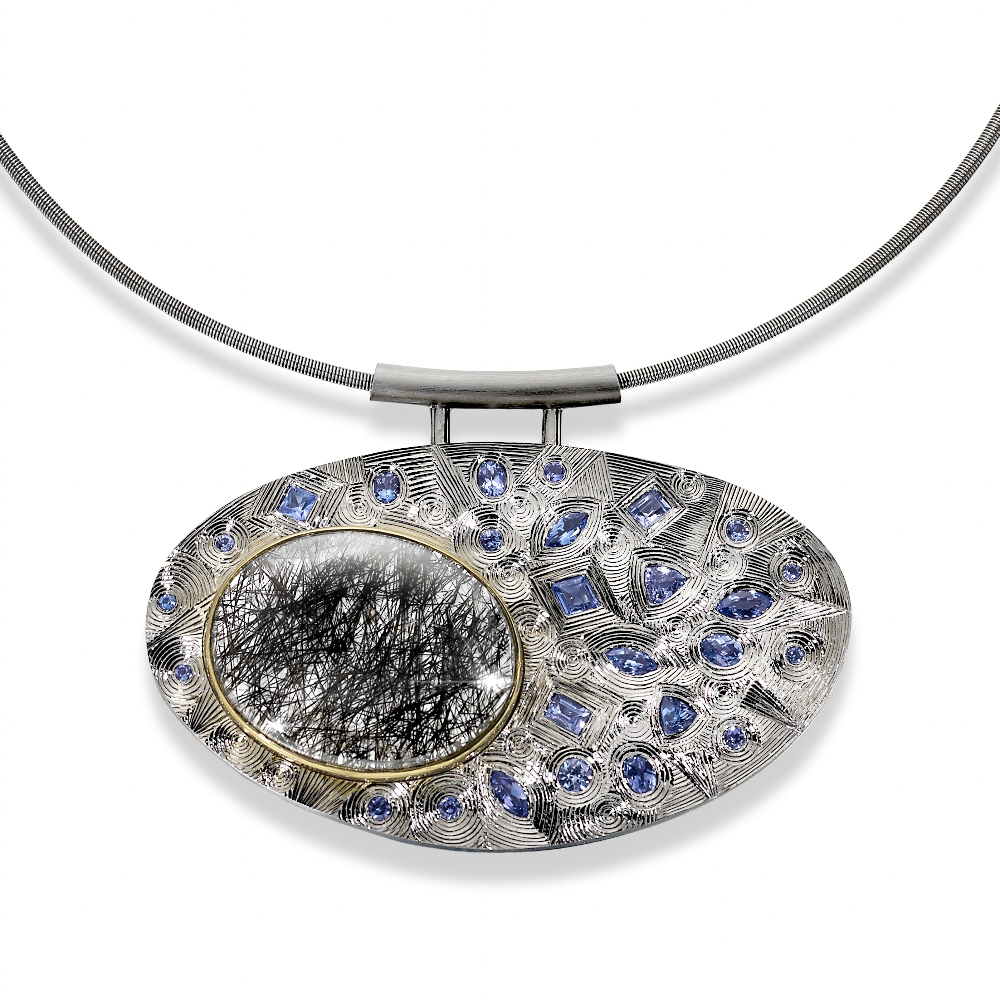"<a href=""/jewellery/silver-finished-grey-rhodium-hand-engraved-set-various-shaped-tanzanites-and-one-oval"">Silver finished in grey Rhodium. Hand engraved. Set with various shaped Tanzanites and one oval Rutilated Quartz set in yellow gold. Stainless steel chain. Photo: Simon B Armitt.</a>"