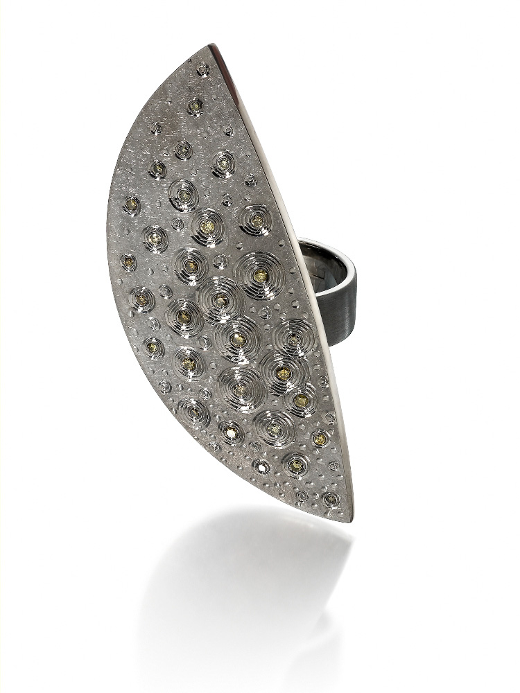 "<a href=""/jewellery/dress-ring-silver-finished-light-and-dark-grey-rhodium-hand-engraved-set-yellow-green"">Dress Ring  Silver finished in light and dark grey rhodium, hand engraved, set with yellow / green diamonds.  Phot : Simon B Armitt</a>"