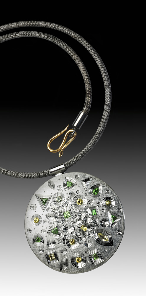 "<a href=""/jewellery/spring-pendant-silver-hand-engraved-finished-grey-rhodium-plate-set-yellow-and-grey"">SPRING PENDANT. Silver hand engraved, finished in grey rhodium plate. Set with yellow and grey sapphires, also green garnets. Approx 60 mm diam 2009/10. Chain also in silver, grey rhodium plated. Photo Simon B Armitt.</a>"