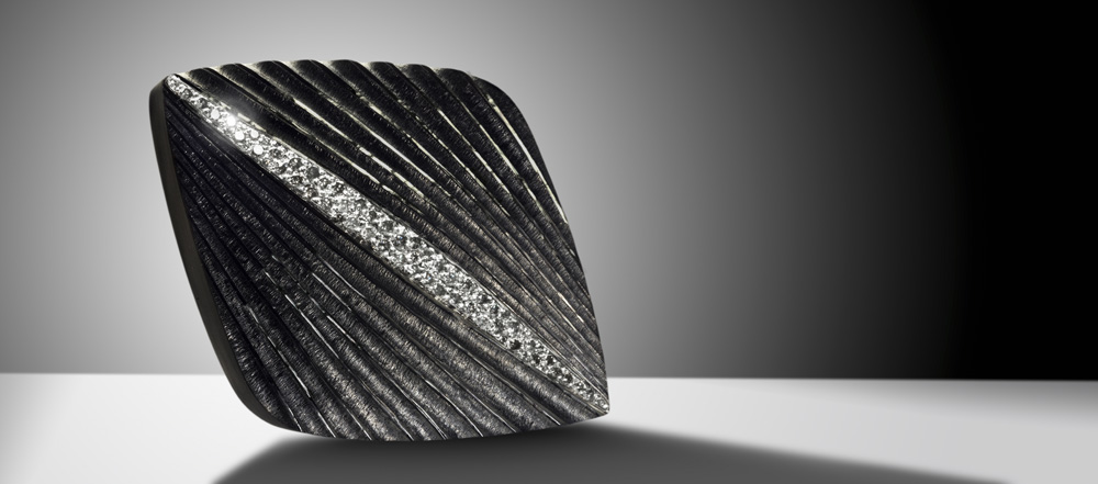 "<a href=""/jewellery/comet-brooch-silver-hand-engraved-and-carved-finished-black-rhodium-pave-set-grey-and"">COMET BROOCH. Silver hand engraved and carved, finished in black rhodium, pave set with grey and white diamonds. 50mm x 30mm. Photo: Simon B Armitt</a>"