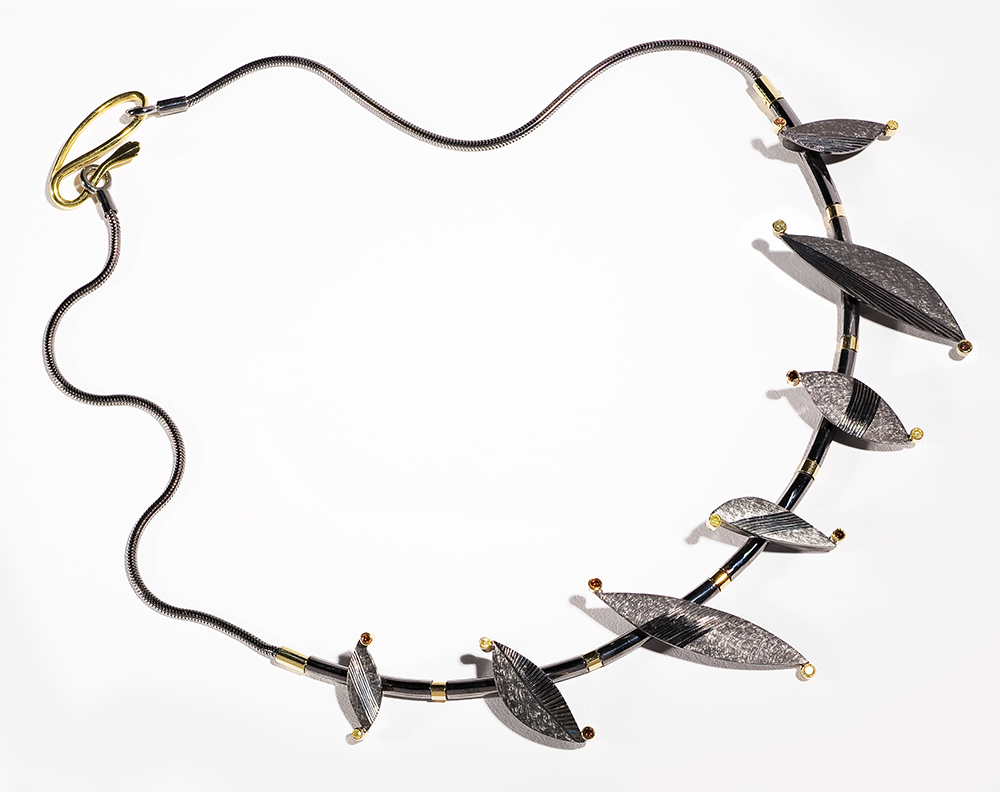 "<a href=""/jewellery/chaos-necklace-silver-black-rhodium-plated-18-ct-gold-details-set-natural-yellow-and"">&quot;CHAOS&quot; Necklace Silver black rhodium plated, 18 ct gold details. Set with natural yellow and treated orange diamonds. Photo : Simon Armitt.</a>"
