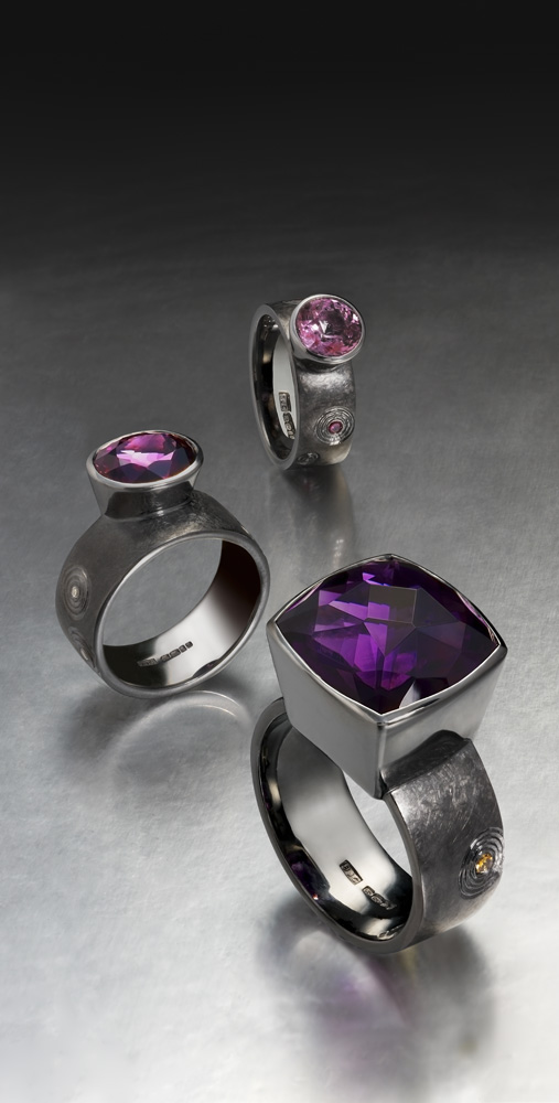 "<a href=""/jewellery/group-cocktail-rings-silver-finished-black-rhodium-hand-engraved-zen-garden-pattern-form"">Group of Cocktail Rings. Silver finished in Black Rhodium. Hand engraved in &quot;Zen&quot; garden pattern form. Amethyst, purple and mauve Spinels, ring shanks set with treated and natural coloured diamonds. Photo Simon B Armitt </a>"