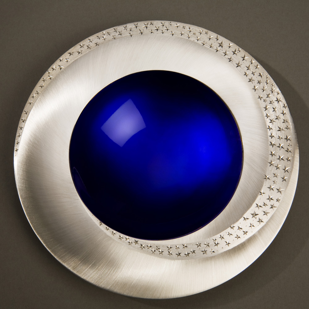 "<a href=""/jewellery/starlight-bowl-150-mm-diameter-britannia-silver-blue-enamel-hand-engraved-brushed-and"">STARLIGHT BOWL 150 mm diameter. Britannia Silver. Blue Enamel, Hand Engraved. Brushed and striated finish. Base polished Limestone. Bowl is designed to spin gently on its stone base. Photo : Simon Armitt</a>"