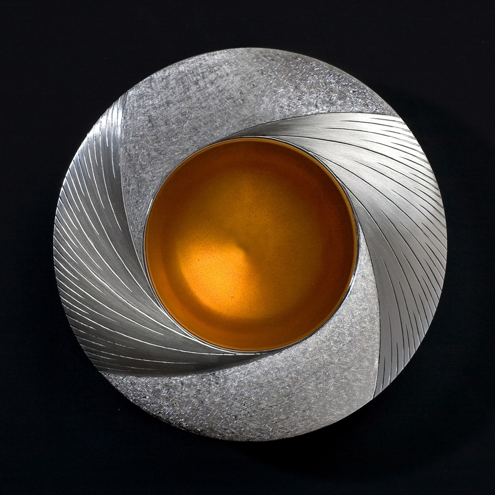 "<a href=""/jewellery/midday-bowl-commission-piece-2009-110-mm-diam-silver-hand-engraved-yellow-orange-enamel"">Midday Bowl Commission piece 2009. 110 mm diam. Silver, hand engraved, yellow / orange enamel. Photo : Simon Armitt</a>"